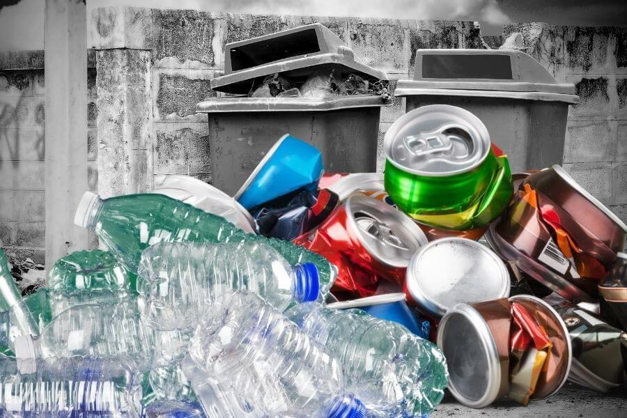 lattine alluminio, barattoli e bottiglie pet ammassate con cestini rotti