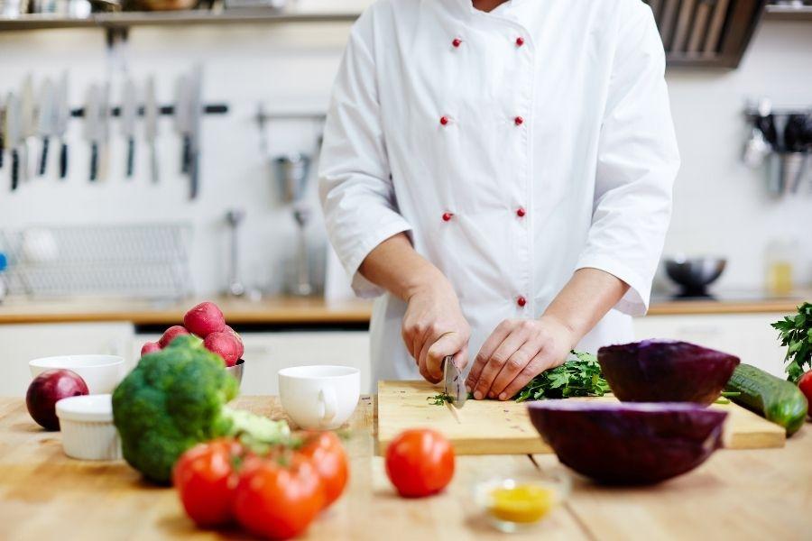 Compostaggio dei rifiuti: cuoco che affetta verdure nella cucina del ristorante